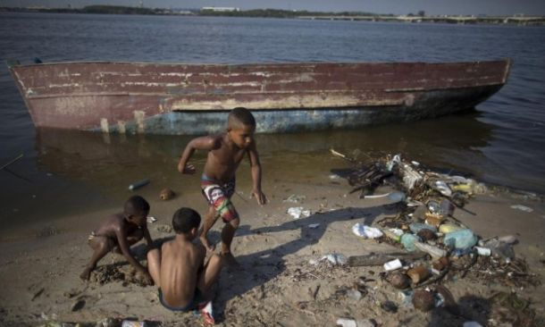 Boys play next to an abandoned boat