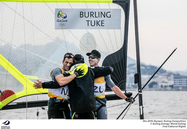 The Kiwis celebrate their Gold medal with their coach. Photo Sailing Energy/World Sailing.