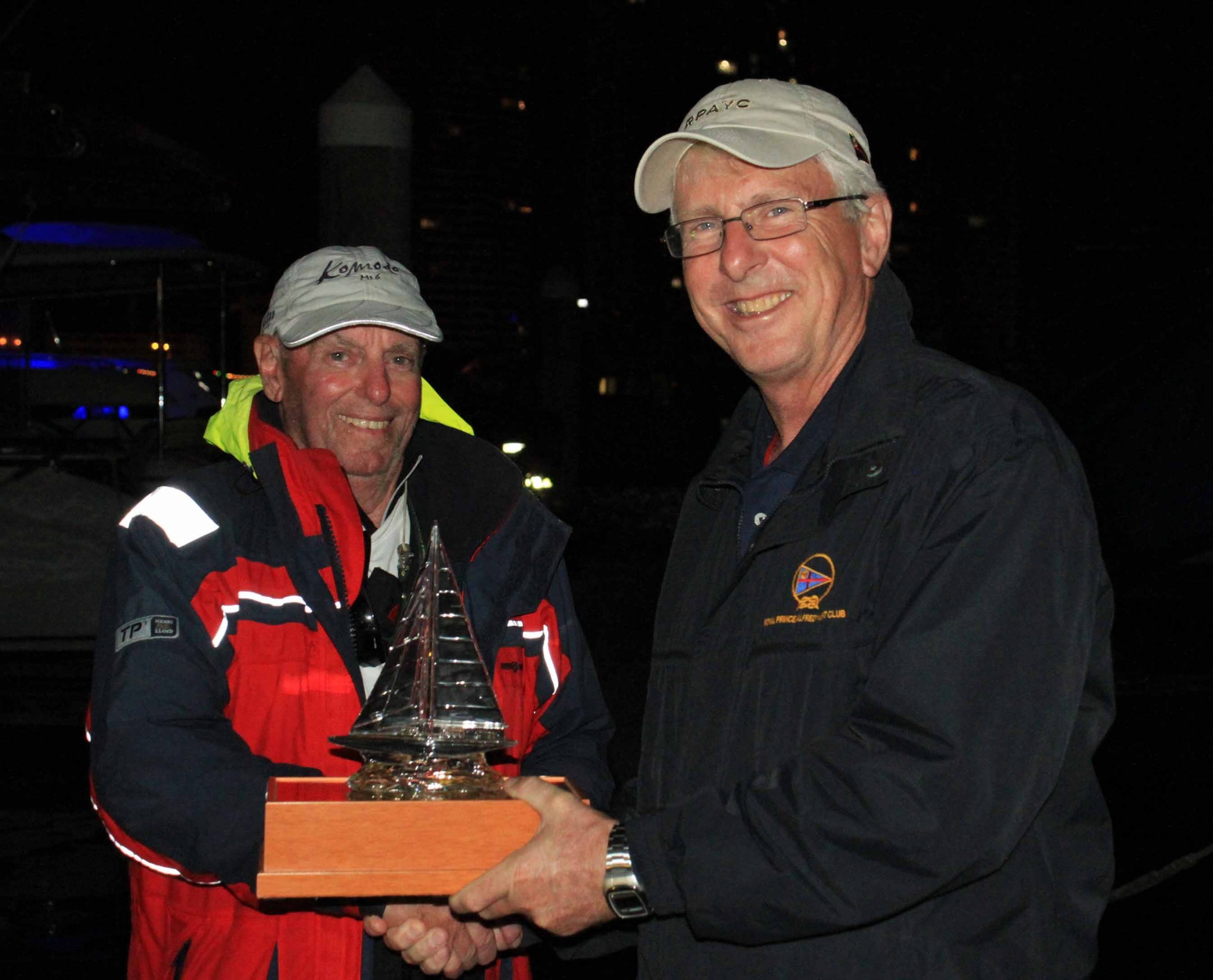 Doug Coulter receives the trophy from Commodore Ian Audsley (right)