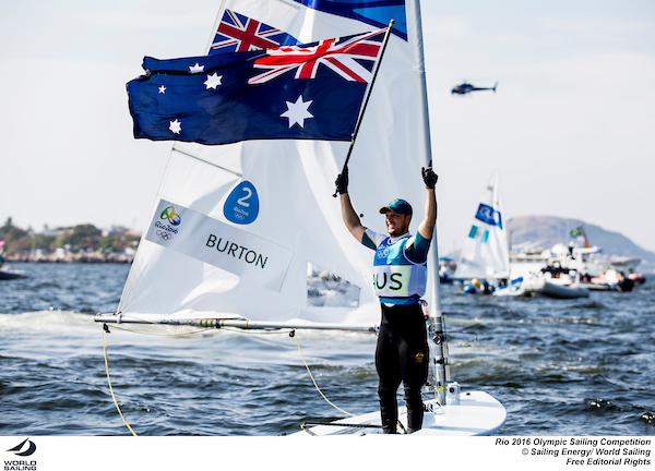 Tom Burton celebrates with the Australian flag. Photo Sailing Energy/World Sailing.
