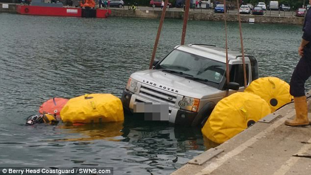 The Land Rover is recovered from the water. Photo Berry Head Coastguard/SWNS.com.