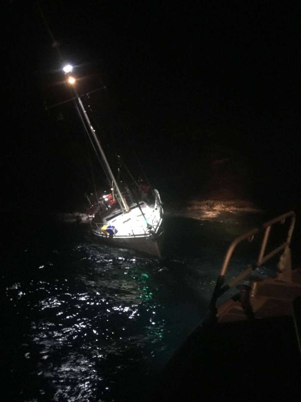 A Coast Guard 45-foot Response-Boat Medium Crew rescues two mariners from the 44-foot sailing vessel Orion grounded and sinking on Molokini Crater May 16