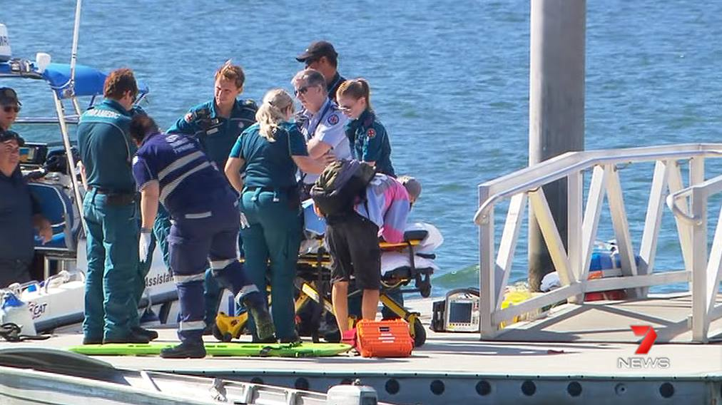 Marine Rescue and ambulance officers transport the man from the dock to the ambulance. Photo Seven News.
