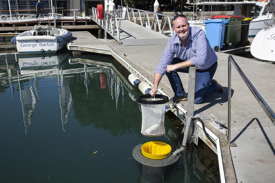 Commodore Paul Billingham with one of the newly installed SeaBins located in the CYCA Marina. Credit - CYCA