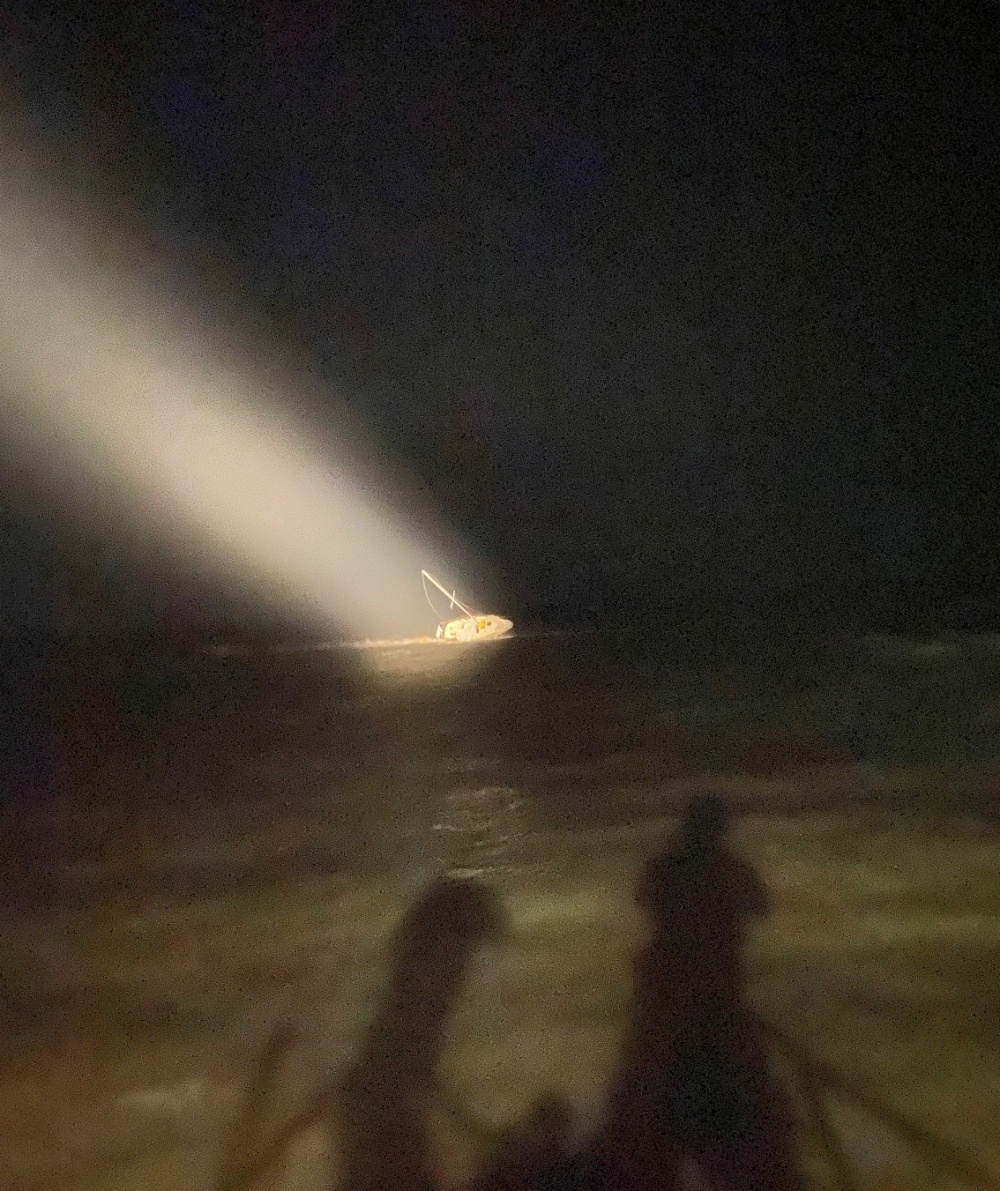 A 30-foot sailboat is disabled and pushed against the north jetty rocks in St. Mary's Inlet