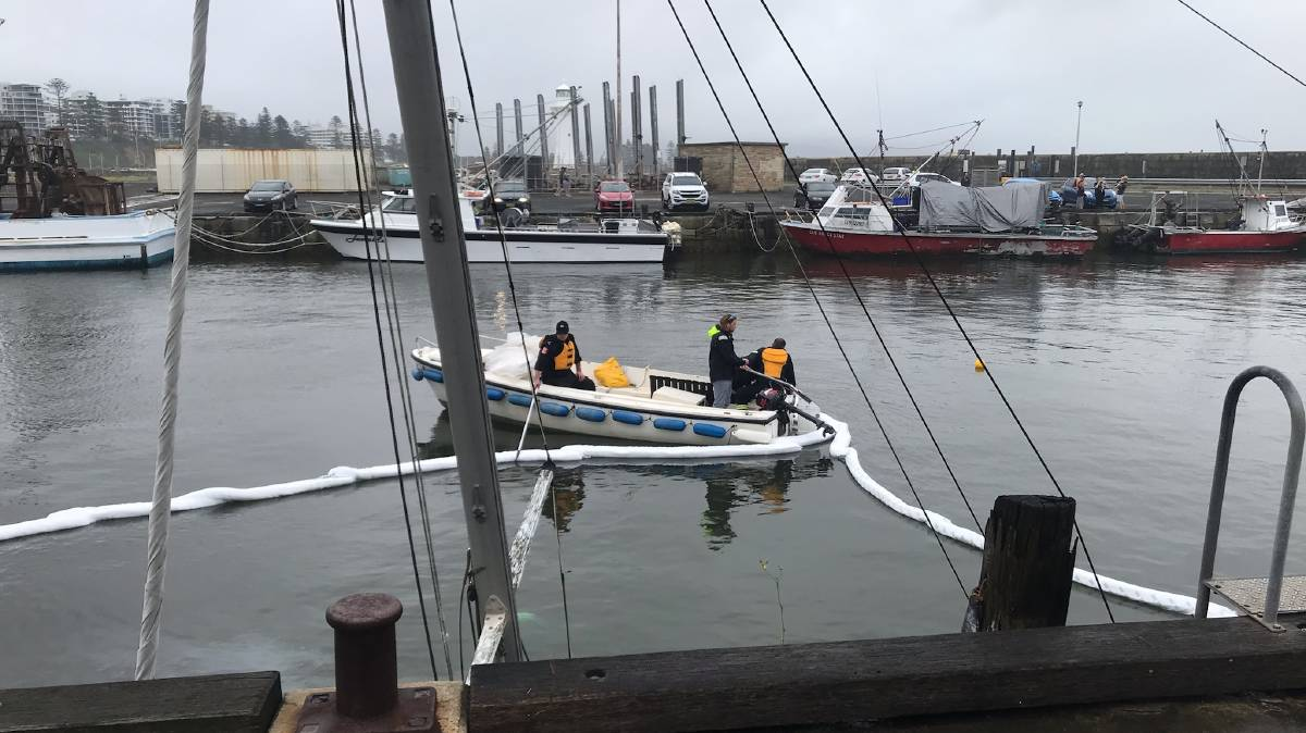 Absorbent booms being laid to contain a slight fuel spill from the yacht that sank in Belmore Basin. Photo Illawarra Mercury.