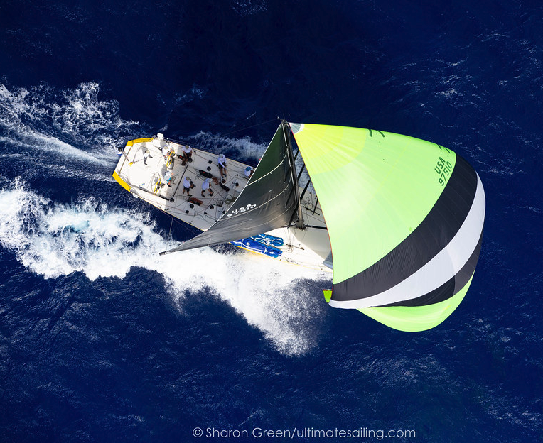 Birds eye view of yacht with kite up