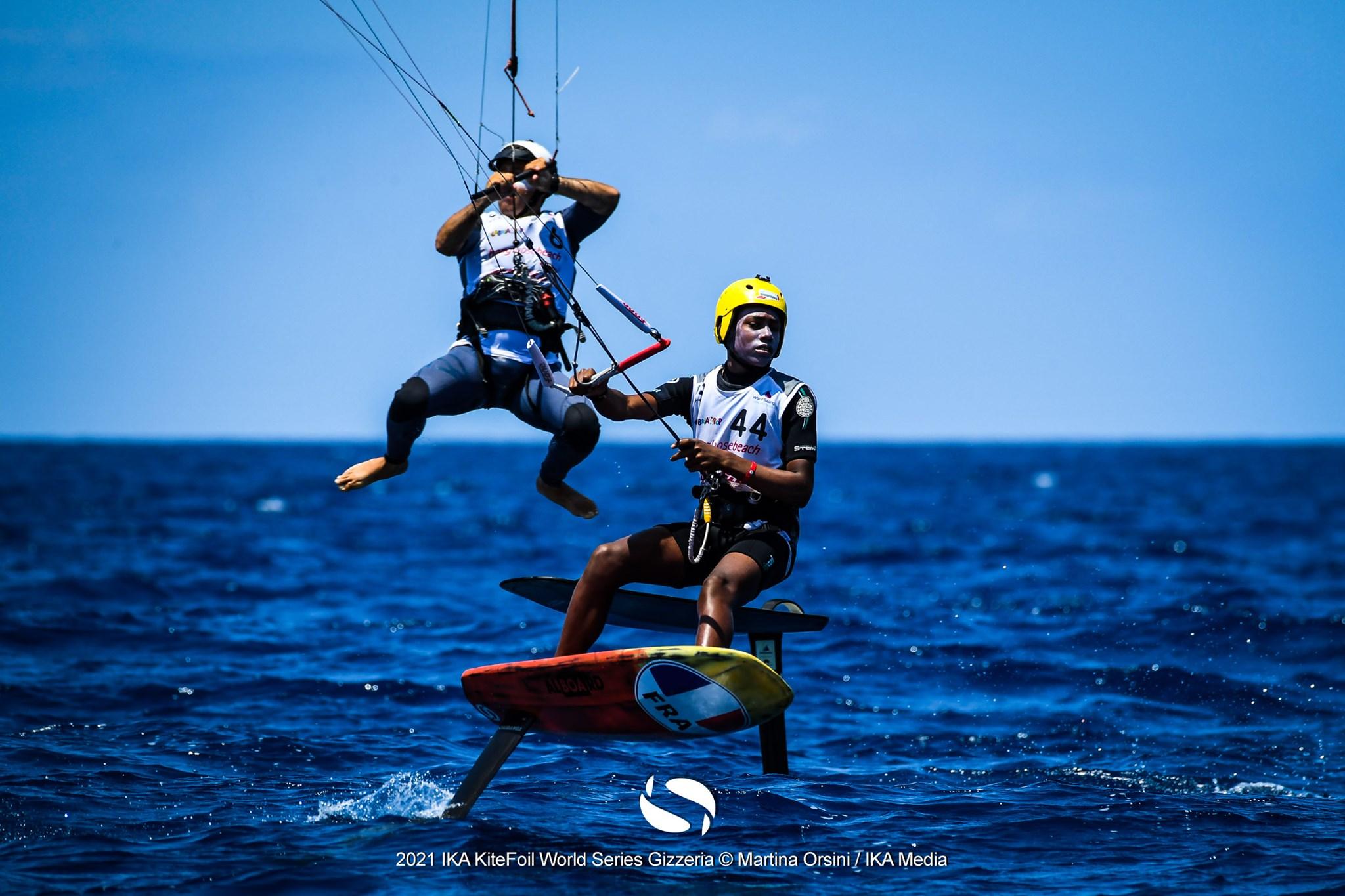 2 kitefoilers. One kitefoiler jumping in the air