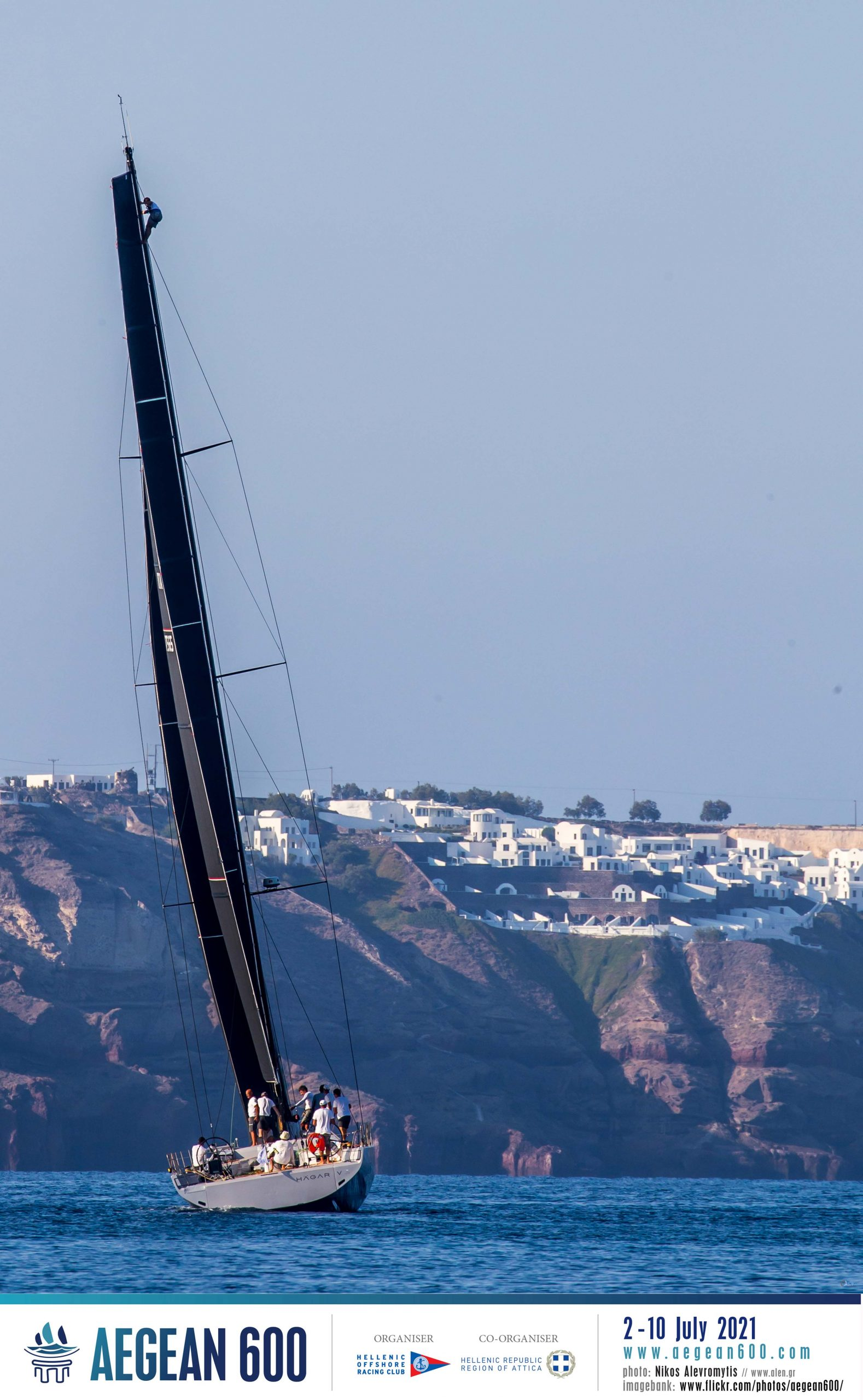 Someone climbing mast as boat sails to finish