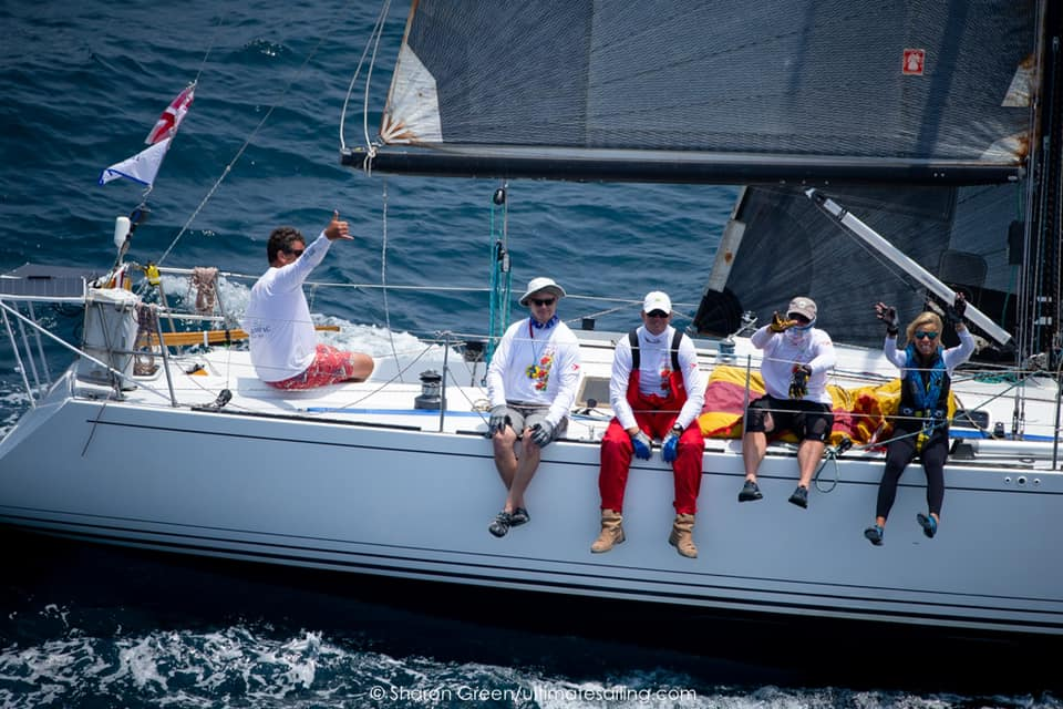 Crew members sitting on the side of the boat