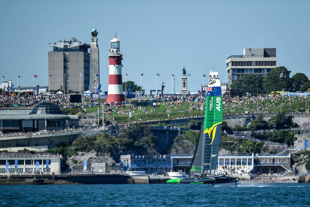 The Australian SailGP Team sailing, in the background - the light house at Plymouth
