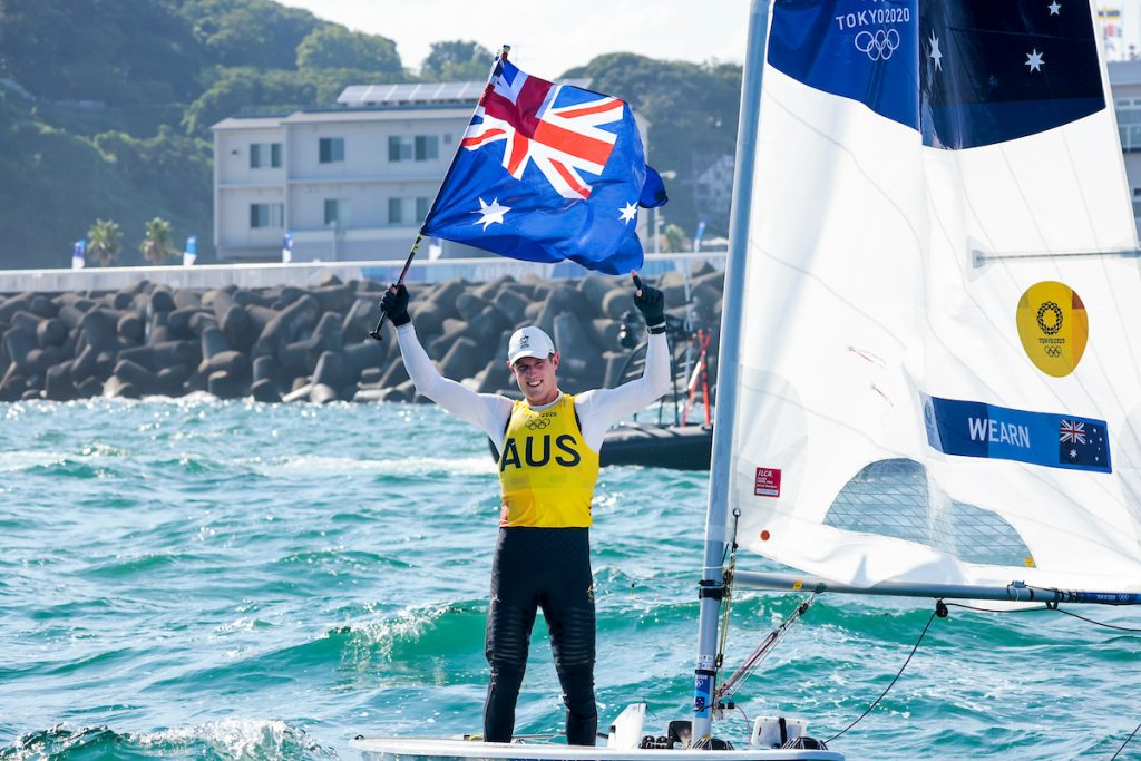 Matt Wearn holding up the Aussie flag, smiling while standing in the laser.