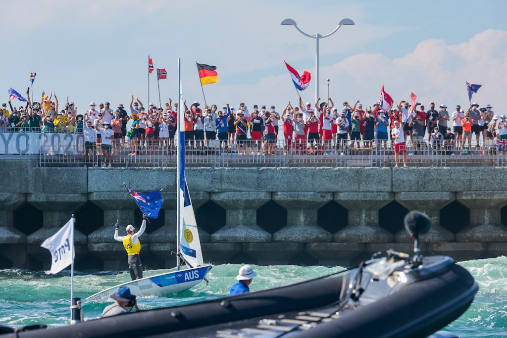 Matt Wearn holding the Aussie flag in front of the sea wall where the Australian Sailing Team cheers him on along with different nations.