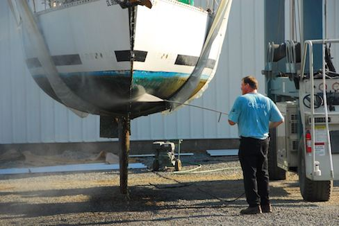 A person antifouling a boat