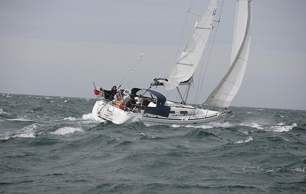A yacht sailing in rough seas.