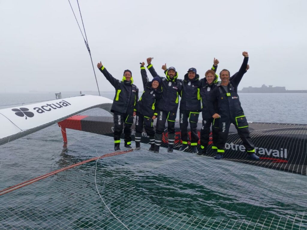 Yves le Blevec and the team on Ultime Actual celebrate after arriving at the finish line.