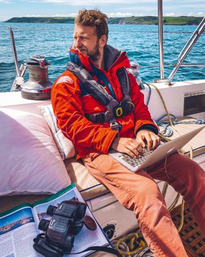 Phil Johnson working on a laptop on his yacht