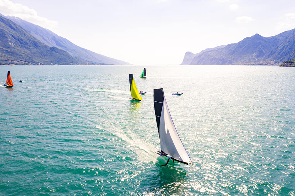 Aerial shot of 69F boats sailing downwind with spinnakers, sun glimmering on the water