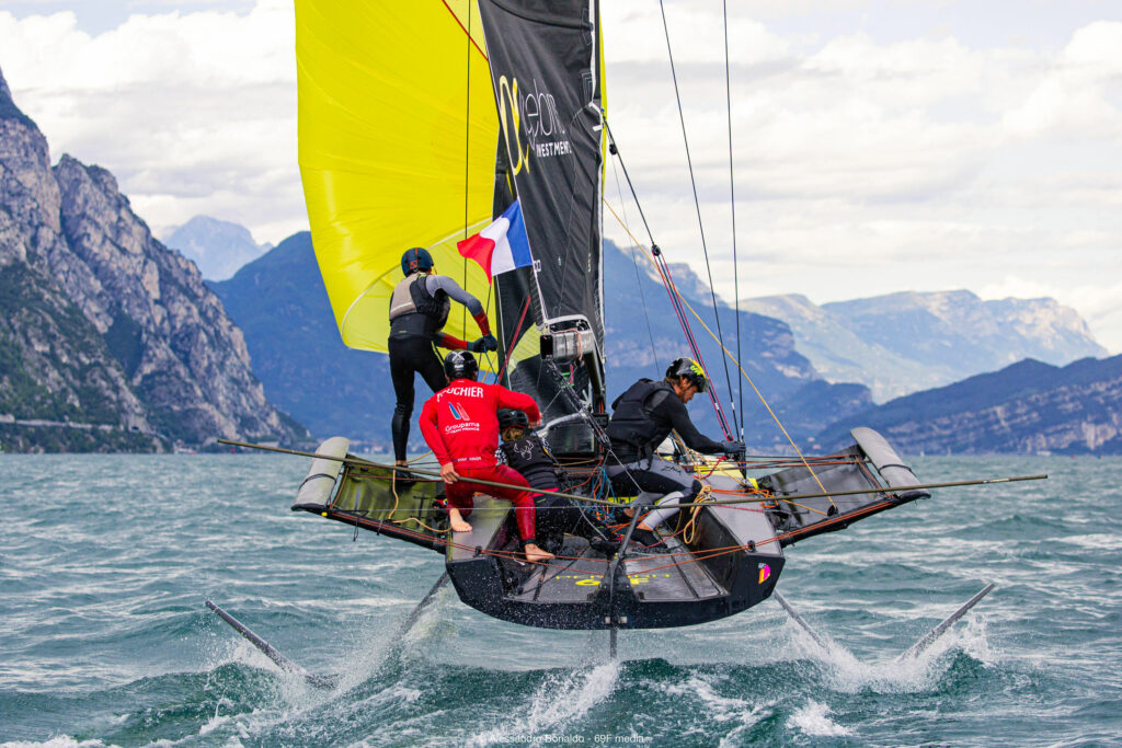 Behind a boat downwind, foiling, about to gybe with the kite up