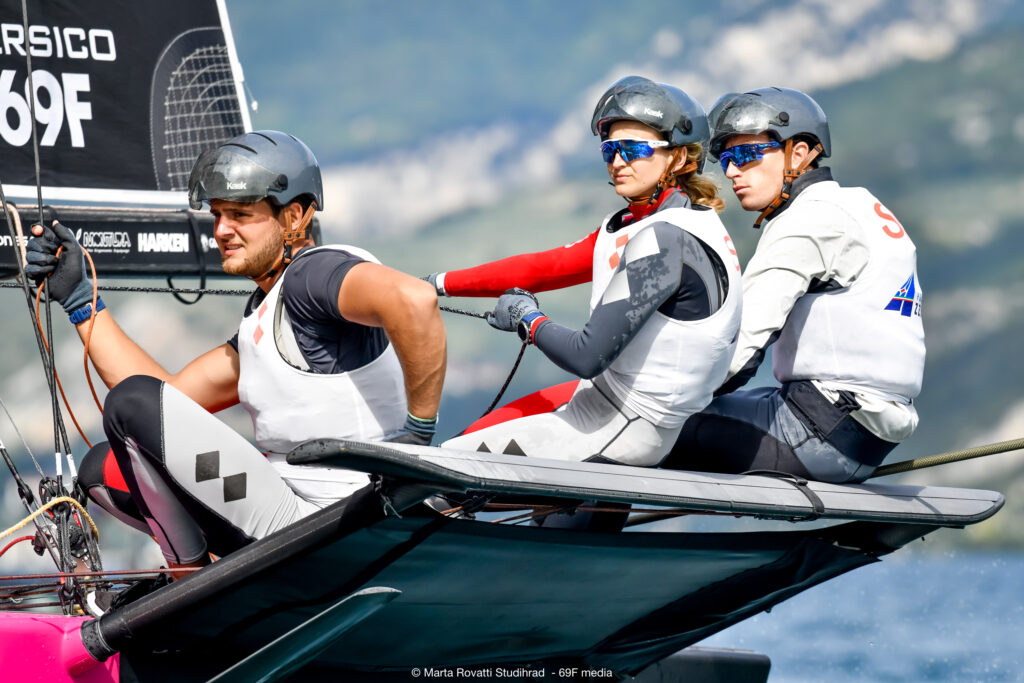 Close-up of three crew members racing.