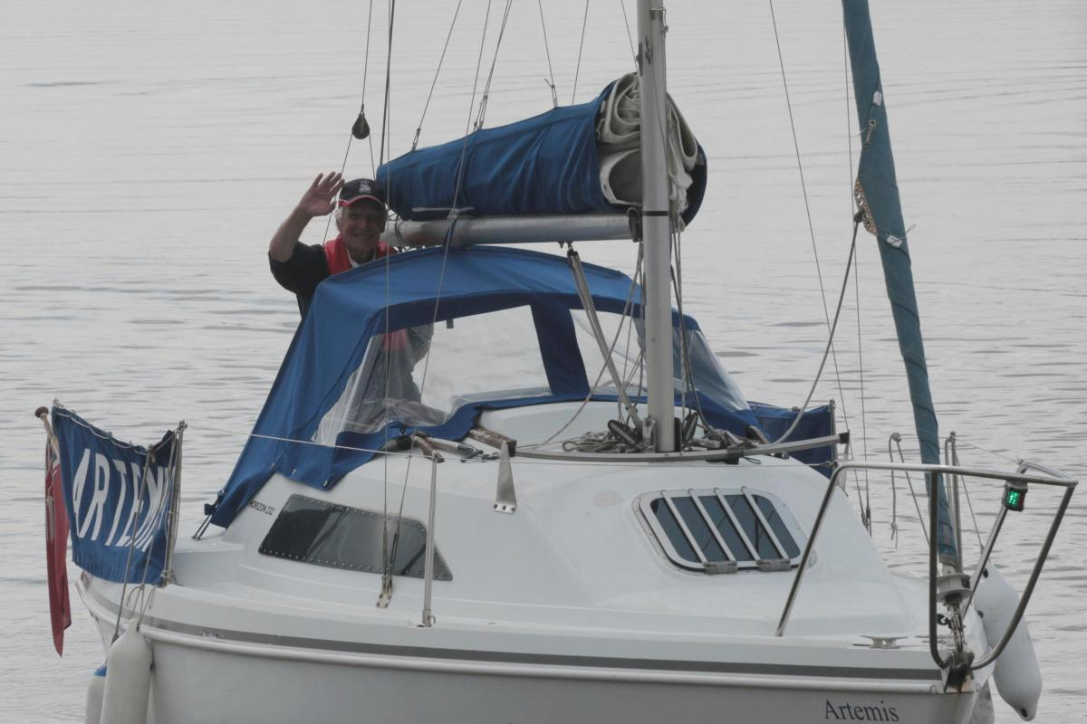 Murdoch McGregor waving from his boat (sails are down)