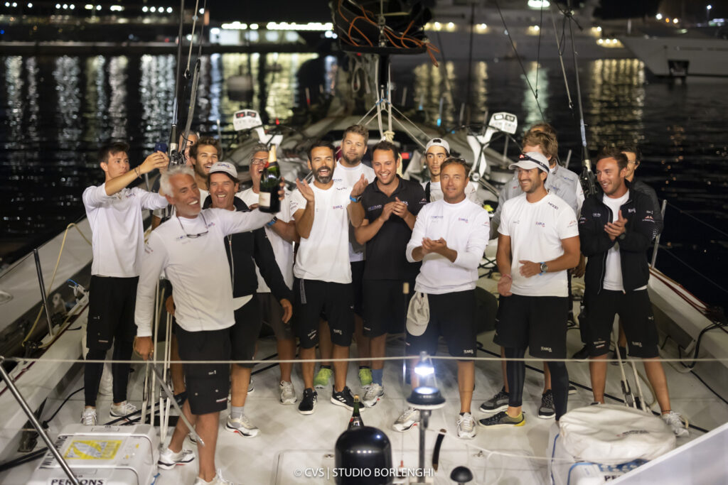 Guido Miani, Furio Benussi and the Arca SGR crew celebrate their line honours victory.