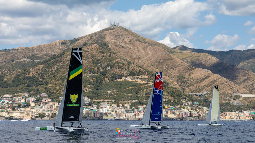 Trimarans sailing with a stunning backdrop of mountains.