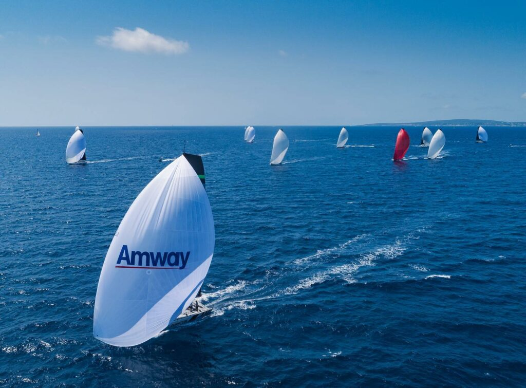 Aerial shot of the fleet sailing downwind with spinnakers.