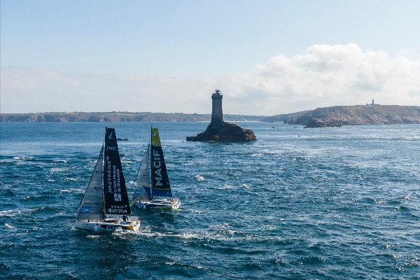 Aerial shot of 2 boats sailing past an island with a lighthouse structure.