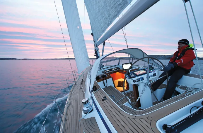 Man steering his yacht at sunset, with chart plotting devices on.
