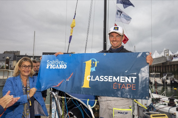 Pierre Quiroga on his boat on the dock holding a winner's banner with officials after Stage 2.