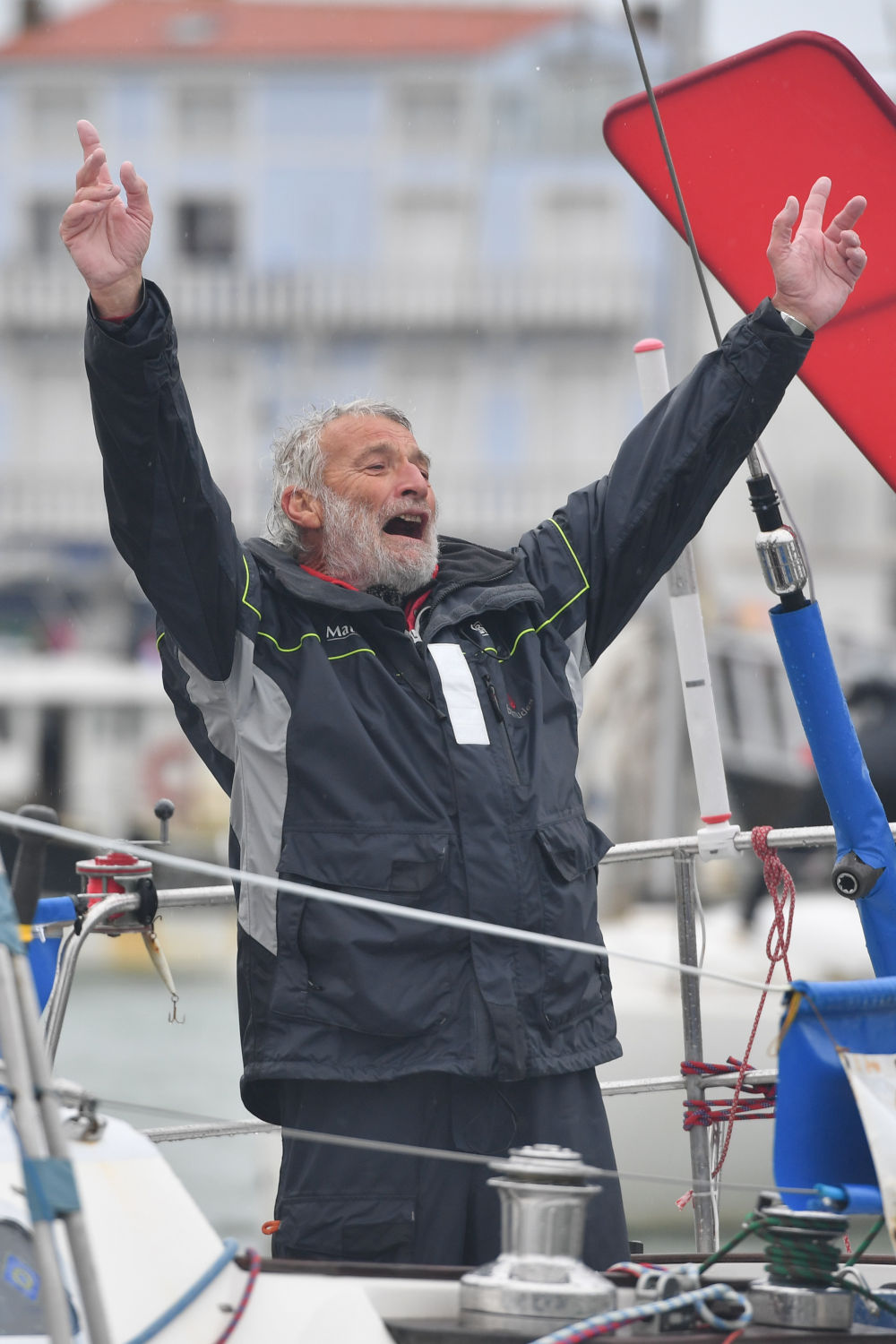 Jean Luc Van Den Heede with his hands up in the air, celebrating his victory on board his boat.