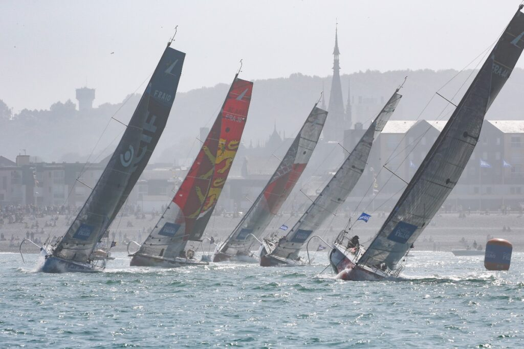 Five boats sailing upwind past a mark with the town in the background.