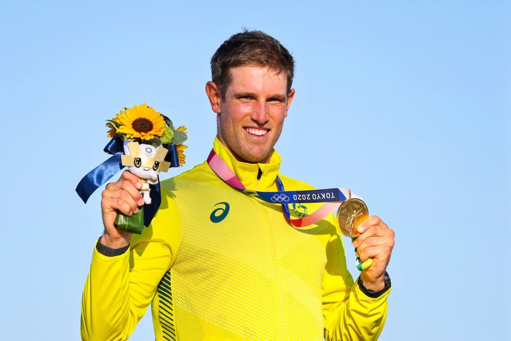 Matt Wearn holding up his medal and flowers at the medal ceremony.