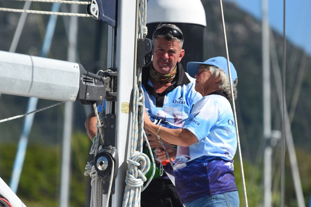 2 people checking the sheets on the mast.