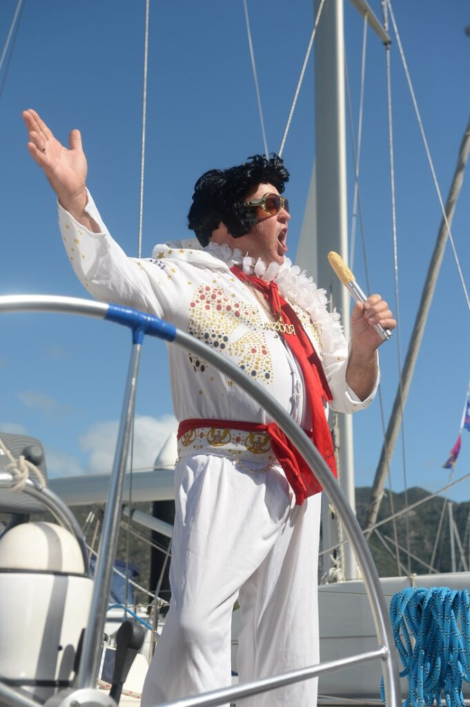 Elvis impersonator singing on a boat in front of the wheel (with tongs as a microphone).