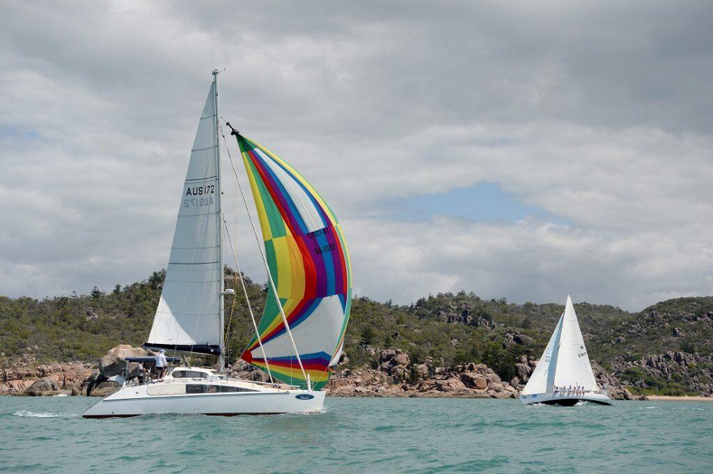 A catamaran sailing downwind with their rainbow kite.