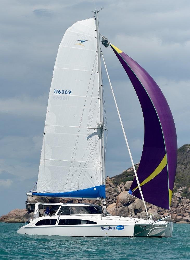 A catamaran sailing downwind with a purple and yellow kite.