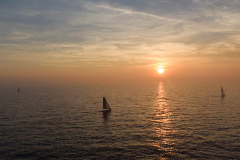 Aerial shot of two boats sailing with the sun setting.