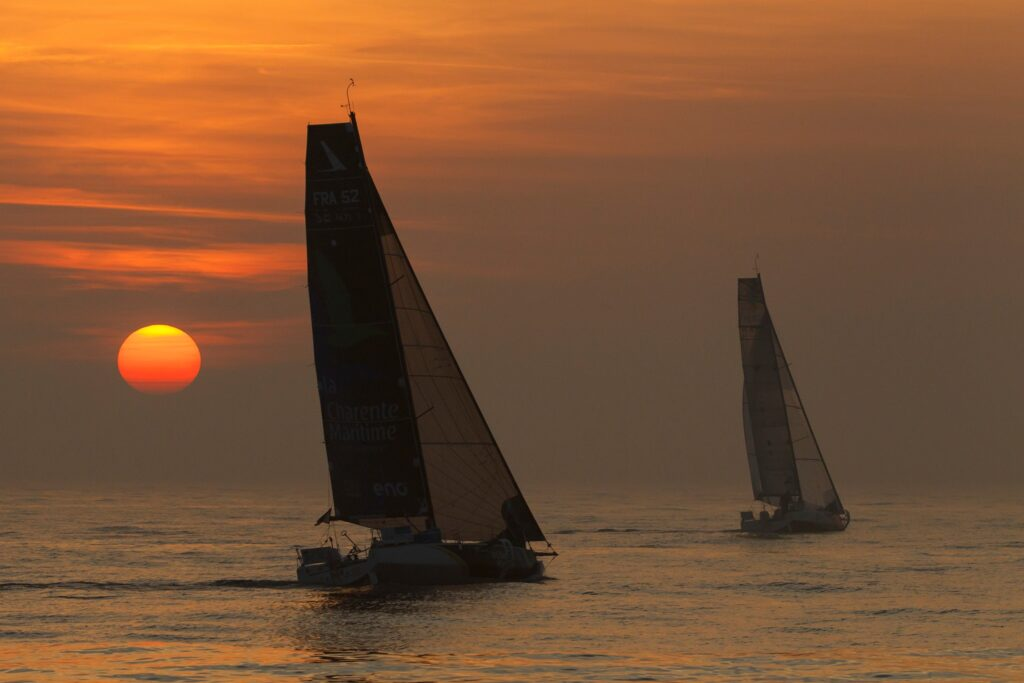 Two boats sailing during sunset on quiet waters.