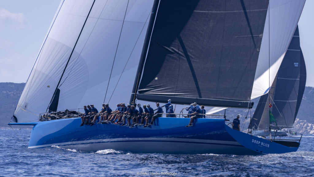 Wendy Schmidt's Botin 85 Deep Blue on a spinnaker reach with another boat in the background. All the crew are on the side of the boat.