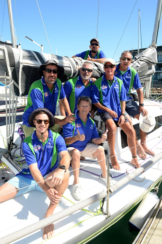 The Wobbly Boot crew smiling aboard their boat on the dock.