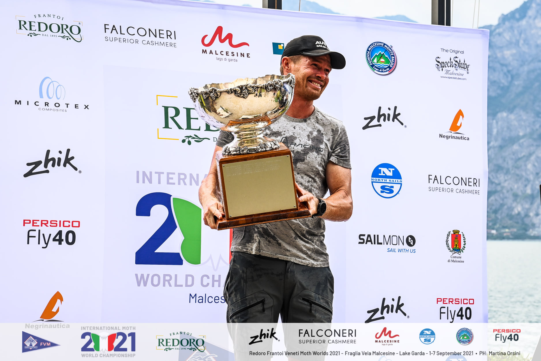 Tom Slingsby holding the cup on the podium.