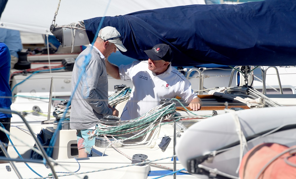 2 people on a yacht preparing the ropes.