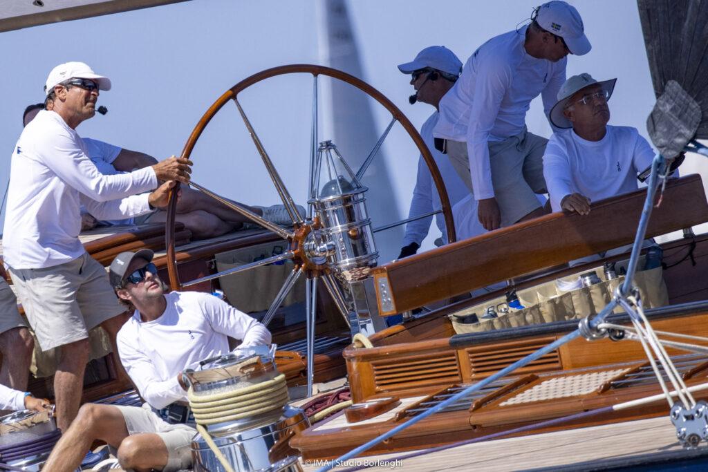 The skipper behind a big wheel.