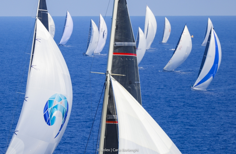 Aerial shot of two masts and behind them a fleet of boats sailing downwind.