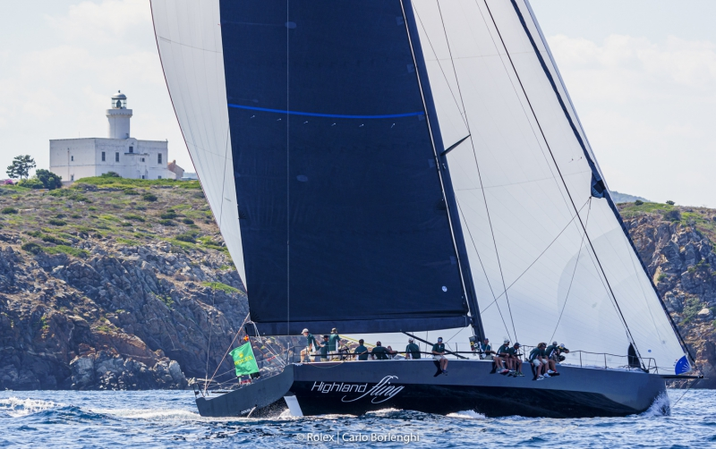 Highland Fling XI on a spinnaker reach passing shore, crew sitting on the side of the yacht.