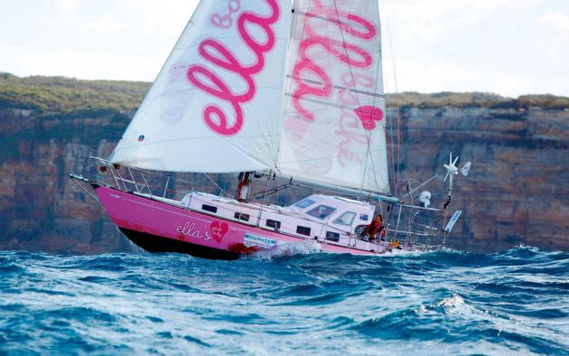 A pink yacht sailing through swell off the coast.