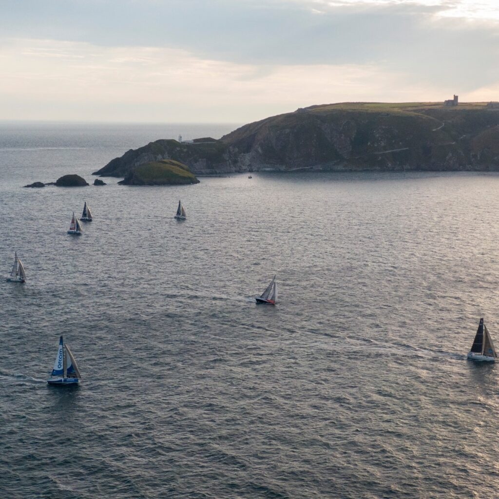 Aerial shot of fleet sailing past a point upwind, late afternoon.