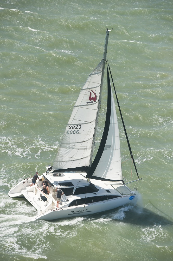Aerial shot of a catamaran reaching with one reef in the main.